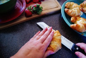 Two hands use a bread knife to slice open a croissant. Other croissants and strawberries are in the background.