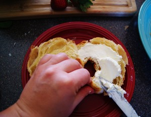 A hand holds a croissant while cream cheese is being spread.