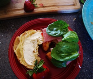 An open croissant with cream cheese on one half and cream cheese, strawberries, ham, and spinach layered on the other.