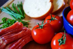 Upclose of ingredients for the Kentucky hot brown, open-faced sandwich, including bacon, chives, tomatoes, and sliced bread.