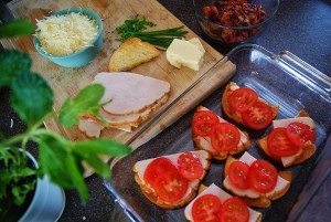 Sourdouch slices in a clearnbaking dish topped with turkey and tomatoes, next to a cutting board with grated Parmesan in a turquoise bowl, sliced turley, chives, toasted bread, and a chunk of white cheddar.