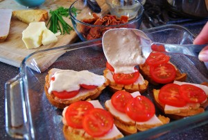 Slices of sourdough topped with turkey and tomatoes with Mornay sauce being spooned over the topped. A chunk of white cheddar, chopped bacon and chives are in the background.
