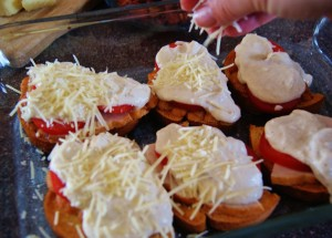 Almost complete Hot Browns in a baking dish being topped with grated Parmesan cheese.