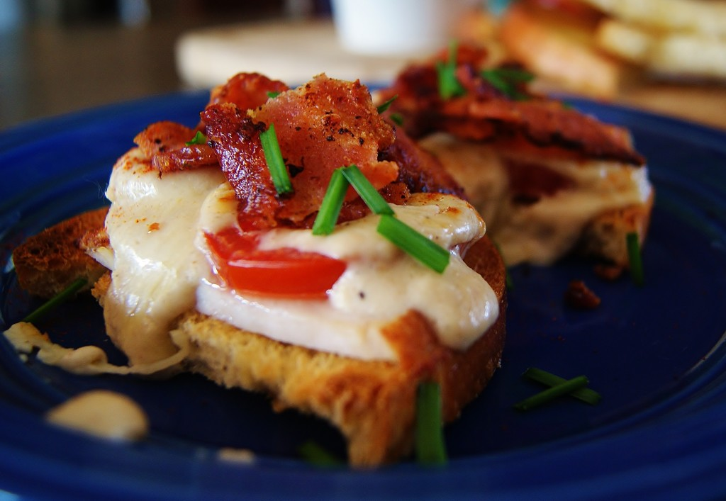 A close up of a traditional Kentucky Hot Brown with bacon and mornay sauce on a blue plate.