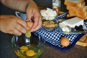 Two hands cracking a brown egg in a glass bowl with the ingredients for the blackberry grilled cheese in the background on a blue and white gingham tea towel.