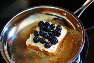 A slice of Texas toast-style bread topped with fontina cheese and blackberry french-toasting in a stainless steel skillet with browned butter.