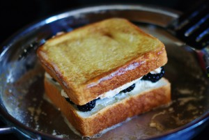 Close up of French-toasted blackberry grilled cheese toasting in a stainless steel skillet. One side is golden brown.