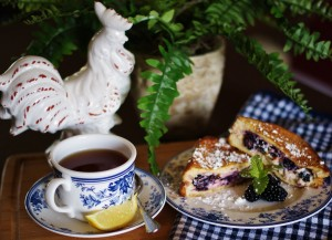 A french-toasted blackberry grilled cheese is pictured brunch style with a white rooster, a cup of tea with a slice of lemon and a spoon, a blue and white gingham tea towel and a fern in the background.
