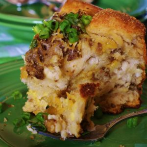 A slice of the sausage, egg and cheese brunch cake on light green plate and fork.