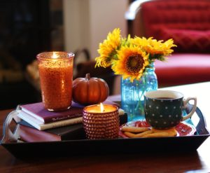 The flicker of the flame and wafts of cinnamon and spice are fundamental to any good fall decor idea.