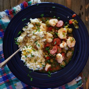 Easy Louisiana Gumbo served with a green chile white rice in a blue bowl with a red, blue, and green plaid fringed napkin and pictured on a weathered butcher block.