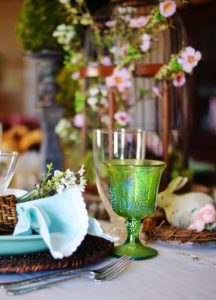 Sideview of place setting. Green goblet, lace-trimmed Robin's egg napkin, and floral centerpiece in background.