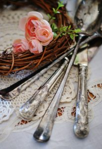 Up close of woodland Easter tablescape antique silver ware over lace with grapevine wreath and rosettes.