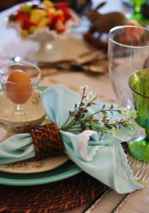 upclose of Woodland Easter tablescape place setting with Robin's egg blue napkin and stem of white flowers.