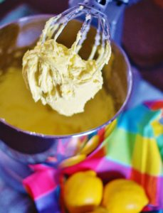 Lemon Buttercream Icing on a whisk attachment for a stand mixer. In the foreground are 3 lemons and a brightly colored pastel checked napkin.