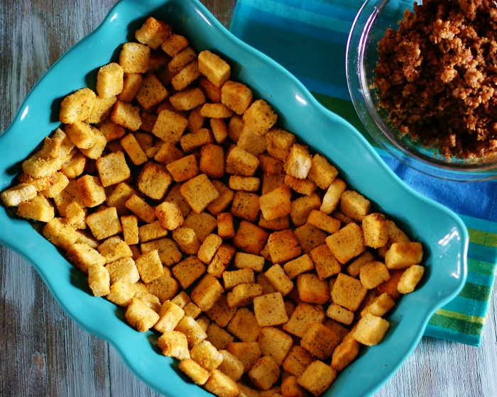 A blue baking dish lined with croutons.