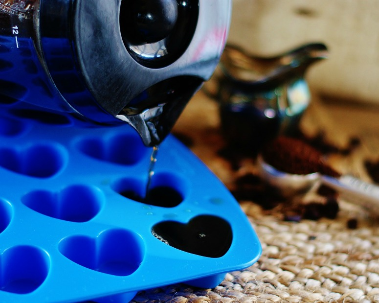 Leftover coffee is being poured from a coffee carafe into a blue silicone heart mold to make coffee ice cubes.