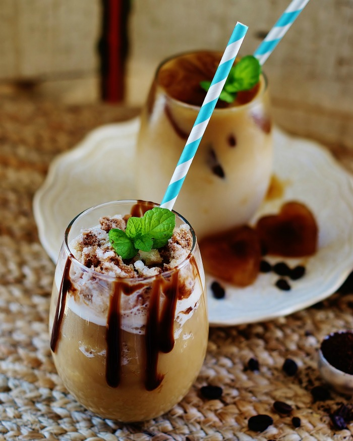 A glass of easy iced coffee and a glass of frozen iced coffee, both made with coffee ice cubes are shown with coffe ice cbues, coffee beans, mint, and striped straws on a grass mat.