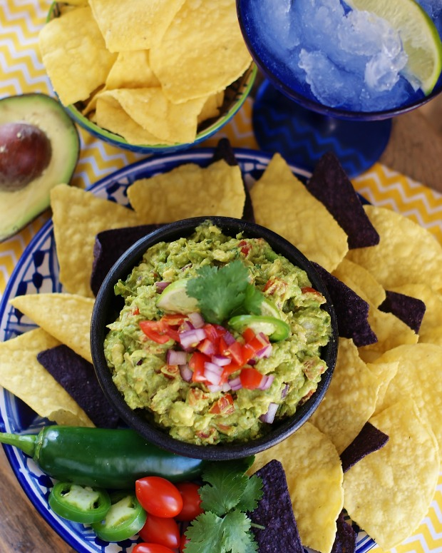 An aerial view of fresh homemade guacamole surrounded by blue and yellow corn chips. A half of avocado, blue magarita style glass, and yellow and white chevron napkin are in the background.
