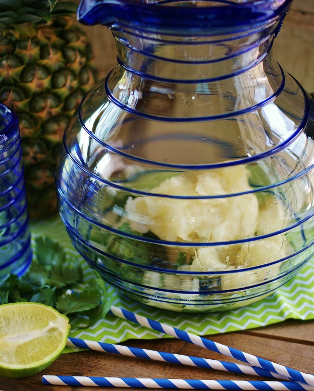 Blue-lined Mexican glass pitcher with chopped cilantro and frozen limeade in the bottom. Blue and white party straws and lime half are in the foreground.