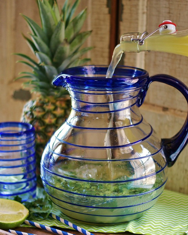Pineapple juice being poured into the blue-lined Mexican glass pitcher. A pineapple, party straws, lime half and a blue-lined tumbler are in the background.
