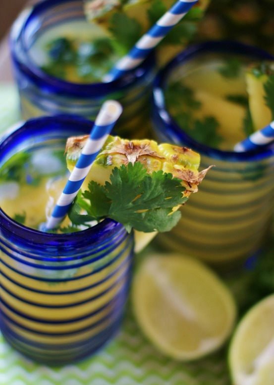 Upclose of pineapple sparkling drink with blue and white party straws, pineapple garnishes, and lime halves.