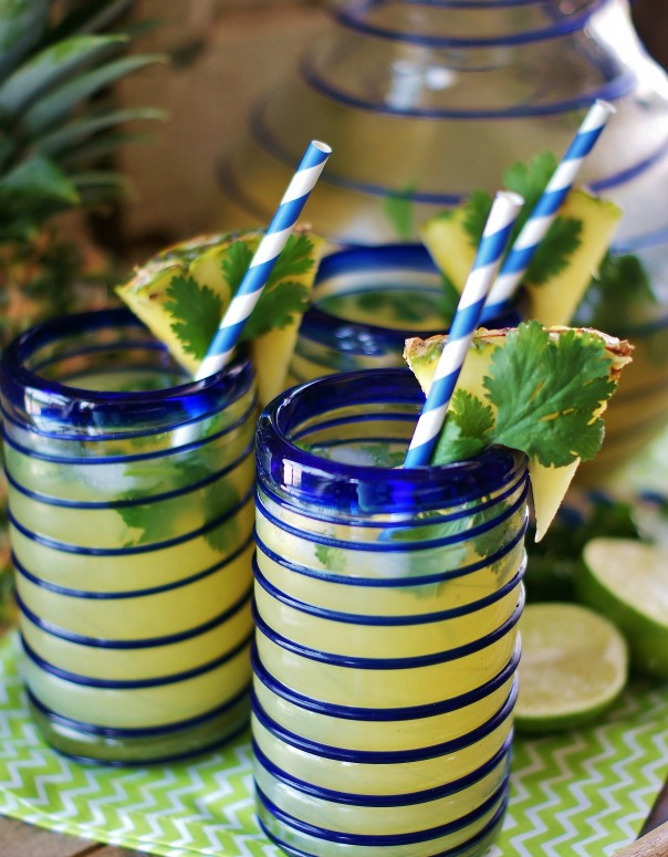 Blue-lined Mexican glass tumblers filled wih Pineapple Cilantro Spritzers, garnished with a wedge of pineapple, a blue striped party straw and cilantro leaf.