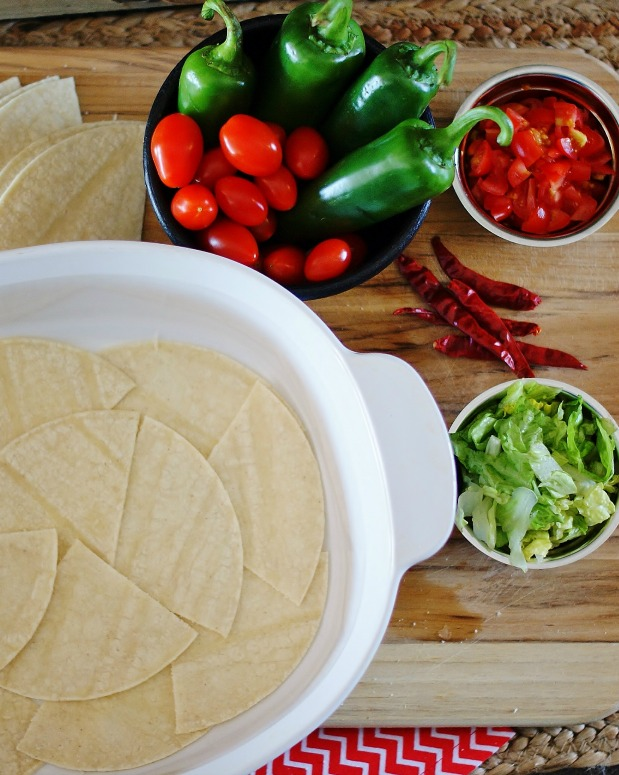 A large white corningware dish with the bottom lined with white corn tortillas cut in quarters.