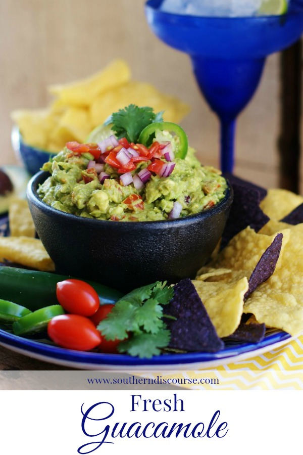 An image of fresh guacamole in a black mortar bowl optimized for Pinterest.
