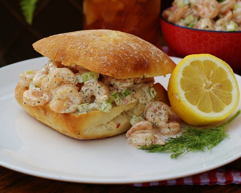 A completed Southern Shrimp Salad Roll on a plate with half a lemon and some dill.