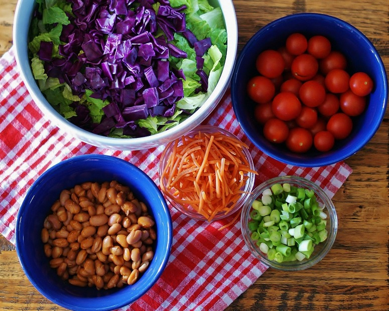 Bowls full of lettuce, cabbage, tomatoes, carrots, onions, and beans for Catalina Taco Salad.