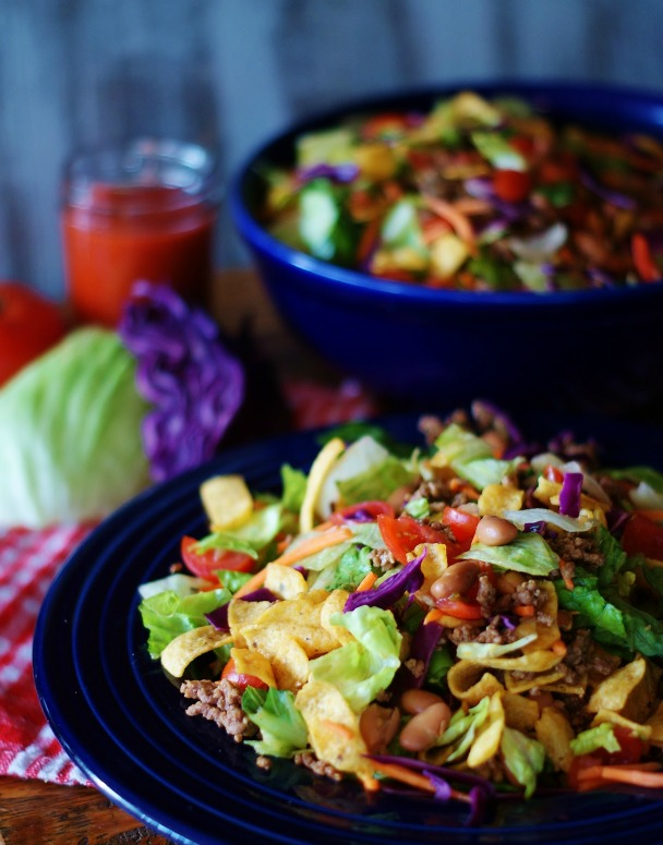Taco salad with corn chips in a blue bowl.