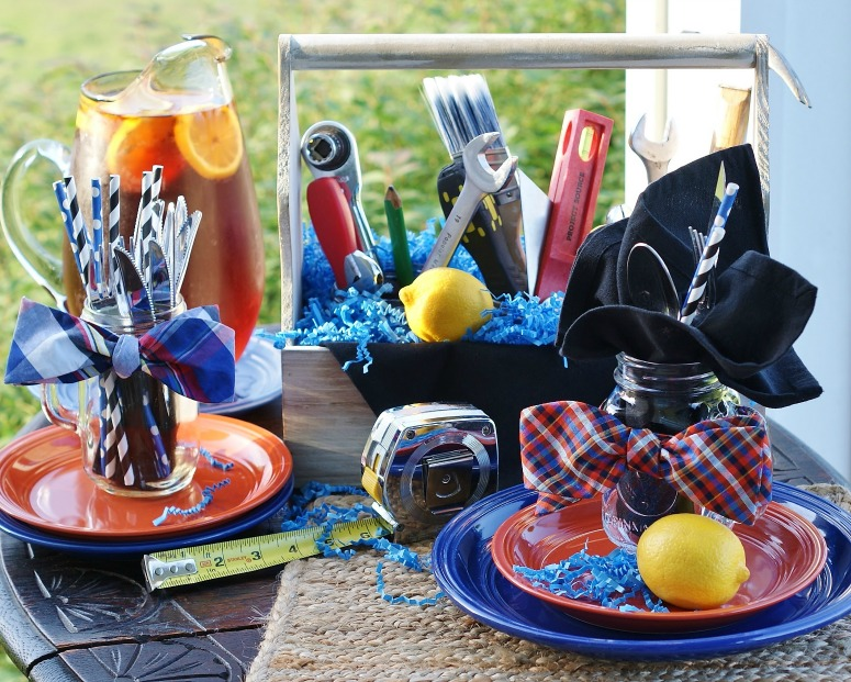 A table set with blue and orange plates stacked, mason jars ted with bowties, and a toolbox centerpiece filled with tools.